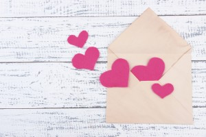 Beautiful old envelope with decorative hearts on wooden background