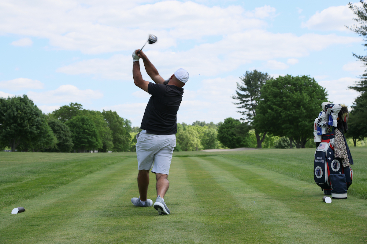 golfer swinging in the Drive for a Difference Golf Tournament